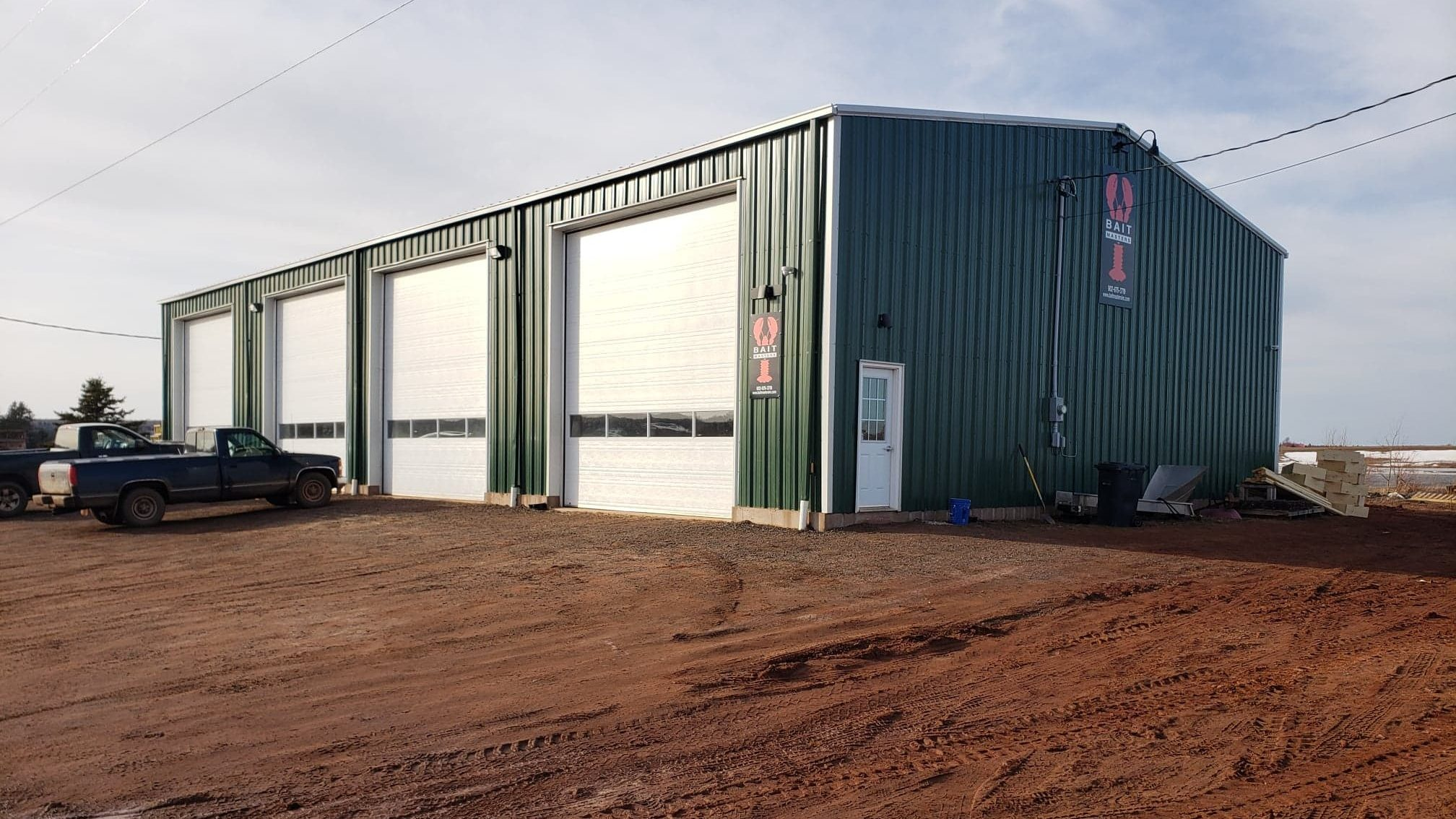 Our P.E.I. facility: a long green building with white doors on red dirt and two trucks parked outside.