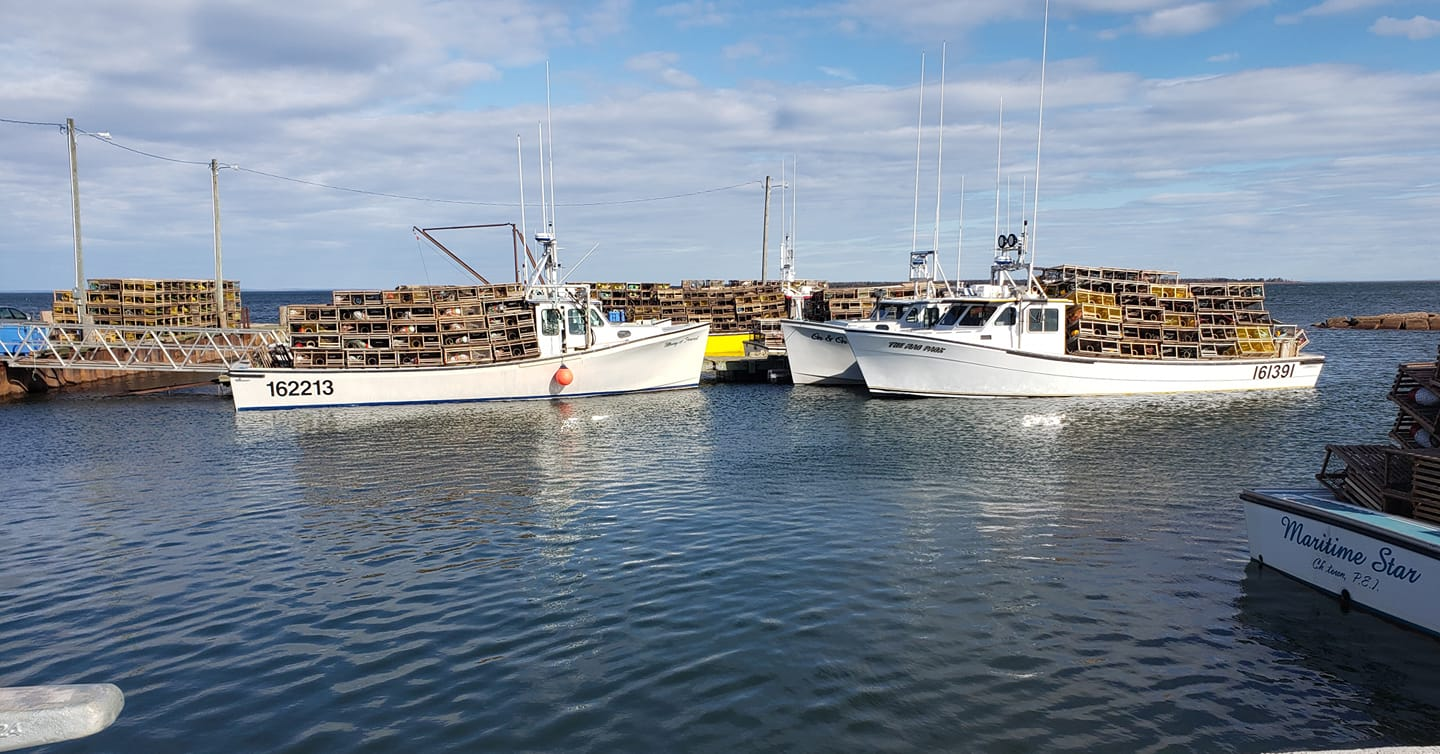 Fishing boats heading out loaded with lobster traps to set in the water.