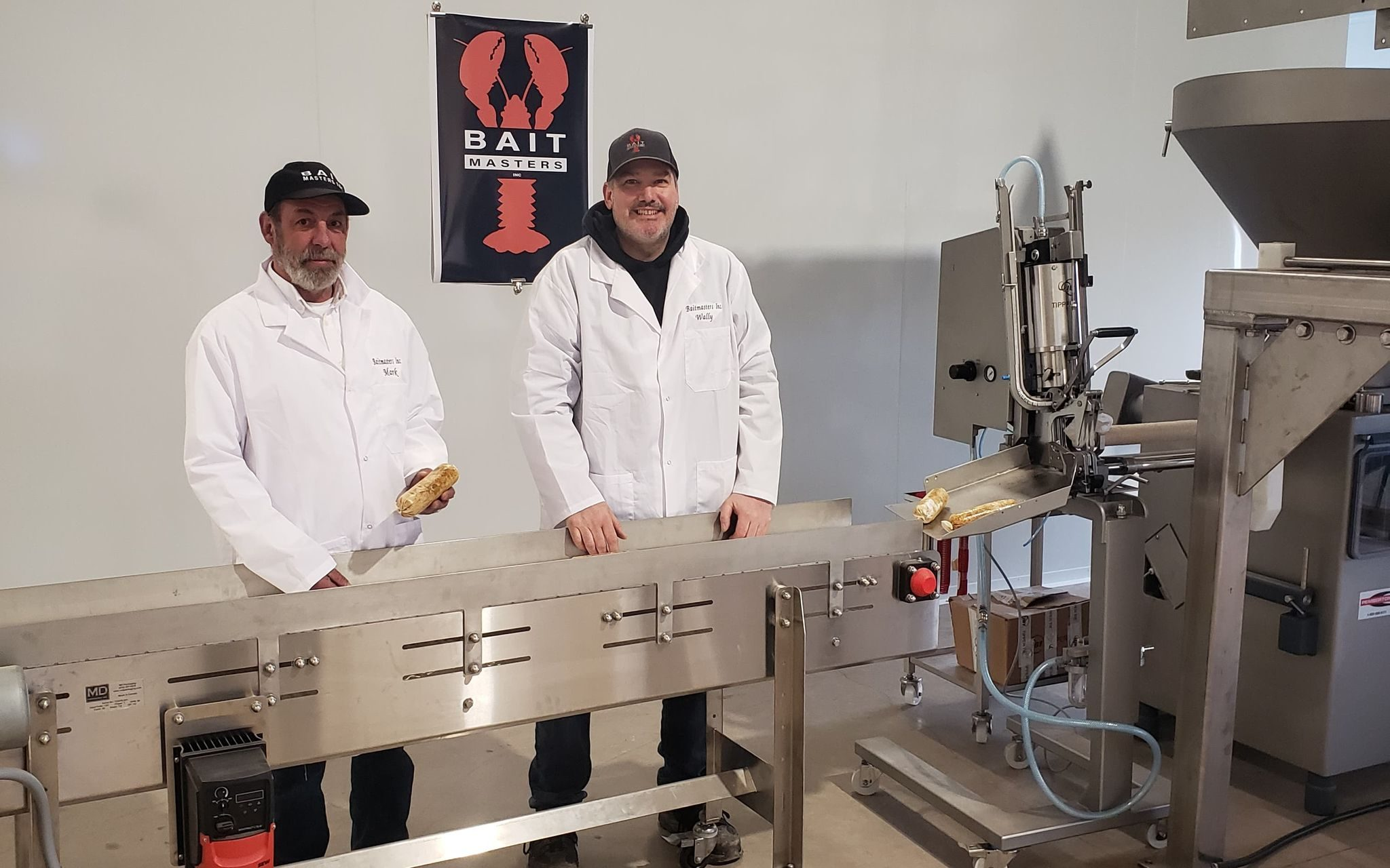CEOs Mark Prevost and Wally MacPhee at a production machine holding bait